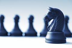 Partes de xadrez e cavalo pretos em uma luz - fundo azul Foto de Stock Royalty Free