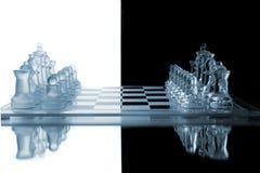 Partes de xadrez em um tabuleiro de xadrez de vidro Fotos de Stock Royalty Free