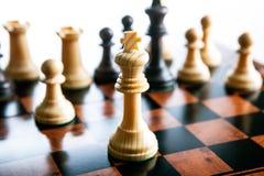 Partes de xadrez em um tabuleiro de xadrez e em uma parte de xadrez do rei Fotos de Stock