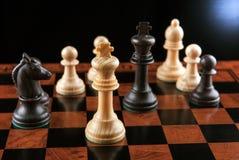 Partes de xadrez em uma tabela do tabuleiro de xadrez e em uma parte de xadrez do rei Foto de Stock