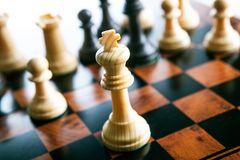 Partes de xadrez em uma tabela do tabuleiro de xadrez e em uma parte de xadrez do rei Imagem de Stock Royalty Free