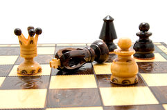 Partes de xadrez no tabuleiro de xadrez com rei caído Foto de Stock Royalty Free