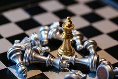 Partes de xadrez de prata perdidas em torno do rei dourado fotos de stock