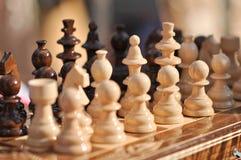 Partes de xadrez preto e branco em um tabuleiro de xadrez, close up O jogo da xadrez figura na placa de jogo Imagens de Stock