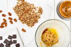 Partes do chocolate e porcas de noz-pecã escuras para a receita das cookies do chocolate da noz-pecã Fotos de Stock