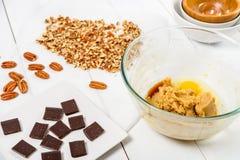 Partes do chocolate e porcas de noz-pecã escuras para a receita das cookies do chocolate da noz-pecã Fotos de Stock Royalty Free
