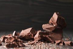 Partes do chocolate em um backround escuro imagens de stock royalty free