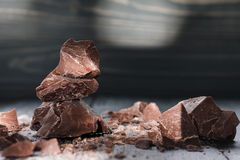 Partes do chocolate em um backround escuro fotos de stock royalty free