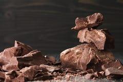Partes do chocolate em um backround escuro imagens de stock