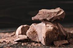 Partes do chocolate em um backround escuro foto de stock