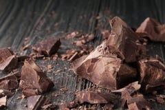 Partes do chocolate em um backround escuro fotografia de stock