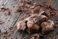 Partes do chocolate em um fundo escuro imagens de stock royalty free