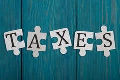Partes do enigma com palavra & x22; Taxes& x22; fotos de stock royalty free