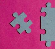 Partes do enigma de serra de vaivém no fundo cor-de-rosa brilhante Fotos de Stock