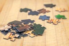 Partes do enigma em um fundo de madeira Fotografia de Stock Royalty Free