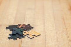 Partes do enigma em um fundo de madeira Imagem de Stock