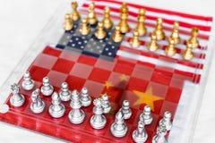 Partes do jogo de mesa da xadrez em EUA e em fundo da bandeira de China, conceito da situação da tensão da guerra comercial fotografia de stock