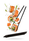 Partes do sushi colocadas entre hashis no fundo branco Fotografia de Stock Royalty Free
