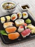 12 partes do sushi em uma placa preta fotos de stock
