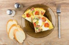 Partes dos ovos fritos com salsicha, tomates na placa, pão Fotos de Stock