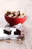 Partes e cookies do chocolate em um copo vermelho Imagem de Stock