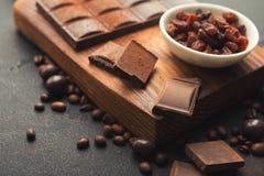 Partes e raisons esmagados do chocolate no fundo cinzento fotografia de stock royalty free