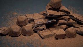 Partes escuras ou do leite do chocolate, p? de cacau e doces org?nicos da trufa no fundo concreto escuro video estoque