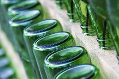 Partes inferiores de muchas botellas vacías verdes que cuelgan en clavos Pare Alco Fotos de archivo libres de regalías