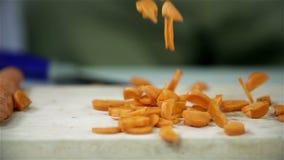 Partes que caen de la zanahoria cortada en un escritorio de madera metrajes