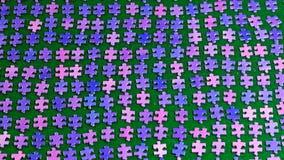 Partes roxas do enigma classificadas em um pano de tabela verde Imagens de Stock Royalty Free