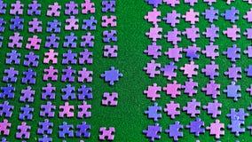 Partes roxas do enigma classificadas em um pano de tabela verde Fotos de Stock