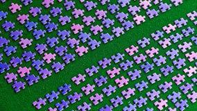 Partes roxas do enigma classificadas em um pano de tabela verde Imagens de Stock