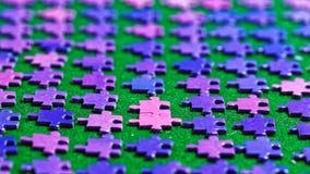 Partes roxas do enigma classificadas em um pano de tabela verde Foto de Stock