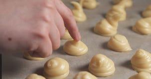 Partes superiores de batida da mão fêmea dos profiteroles com dedo molhado Foto de Stock