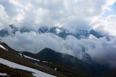 Partes superiores de picos de montanha em um ambiente das nuvens Imagens de Stock