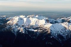 Partes superiores nevado da montanha no por do sol Foto de Stock Royalty Free