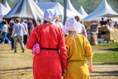 Partes traseiras de duas jovens mulheres nos vestidos medievais no competiam internacional do festival do cavaleiro de St George Foto de Stock