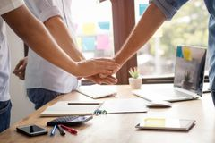 Parthnership and teamwork concept, businessman take hand coordination over table or desk inclued paper graph and planning note t. O get goals stock photo