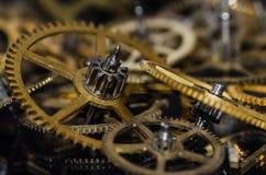 Parti dell'orologio: Raccolta degli ingranaggi metallici d'annata dell'orologio su una superficie nera Fotografie Stock Libere da Diritti