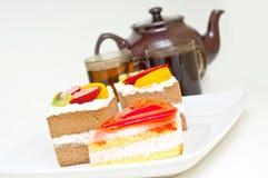 Parti della torta, della teiera e delle tazze di tè contro il whi Fotografia Stock Libera da Diritti