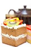 Parti della torta, della teiera e delle tazze di tè contro il whi Fotografia Stock