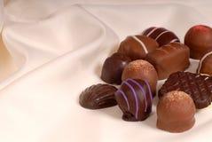 Parti di cioccolato semidolce ed agrodolce su raso beige fotografia stock