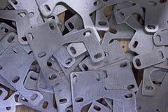 Parti di metallo dal bus che si trova nel mucchio Timbrando i piatti di forma complessa, fatti di acciaio sulle macchine di CNC Fotografie Stock