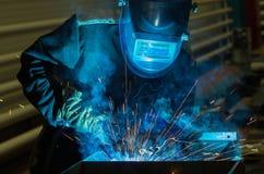 Parti di metallo delle saldature del saldatore in un vestito protettivo Immagine Stock