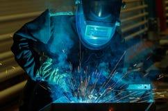 Parti di metallo delle saldature del saldatore in un vestito protettivo Fotografia Stock