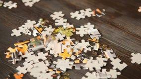 Parti di puzzle che cadono sulla tavola scura archivi video