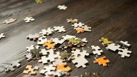 Parti di puzzle che cadono sulla tavola scura stock footage