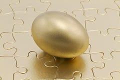 Parti di puzzle con l'uovo di nido dell'oro fotografia stock libera da diritti