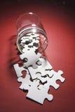 Parti di puzzle del puzzle che straripano vaso di vetro Fotografia Stock