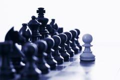 Parti di scacchi nere provocatorie del pegno bianco Immagine Stock
